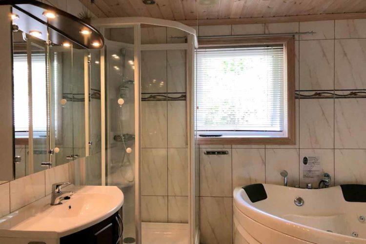Das moderne Badezimmer ist mit einer großen Dusche und einer Badewanne ausgestattet. Foto: Borks