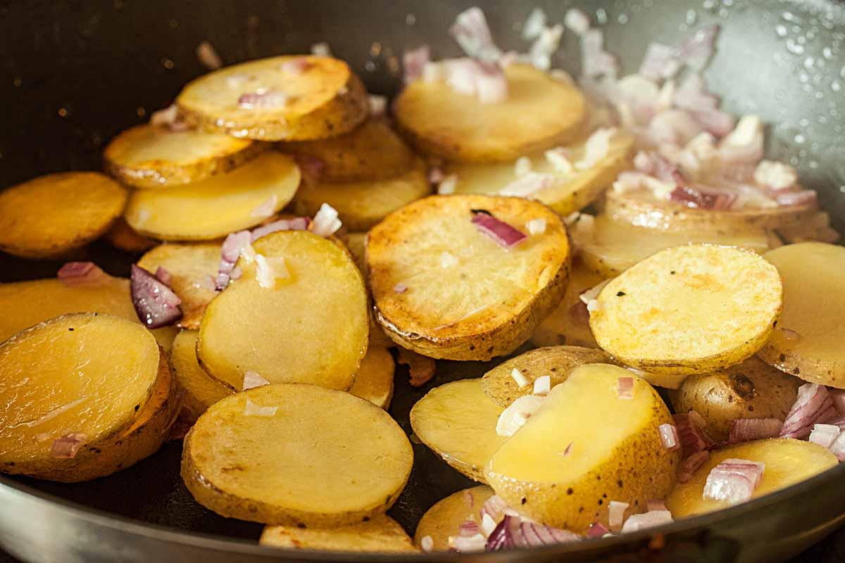 Schneidet die Kartoffeln in Scheiben und bratet sie in der Pfanne an. Zwiebel und Knoblauch kommen kurz vor Schluss dazu! Foto: A. Jagiello