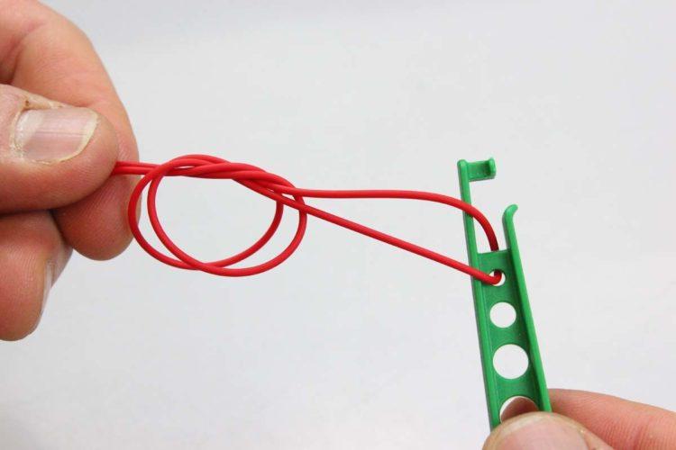 Den Gummi am unteren Ende mit einem einfachen Doppelknoten an die Leiter (Bung) knoten. Erneut das Gummiende bündig abschneiden.