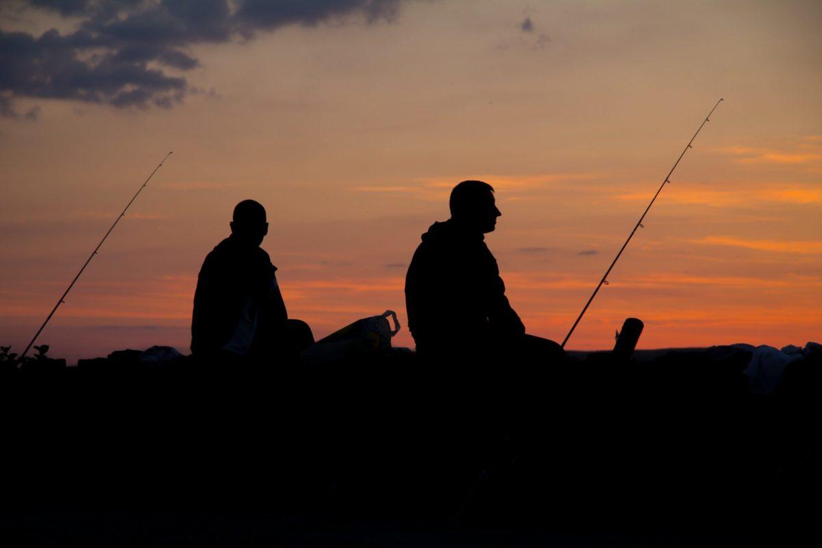 Pfingsten: zwei angler sitzen am Wasser während die Sonne untergeht.