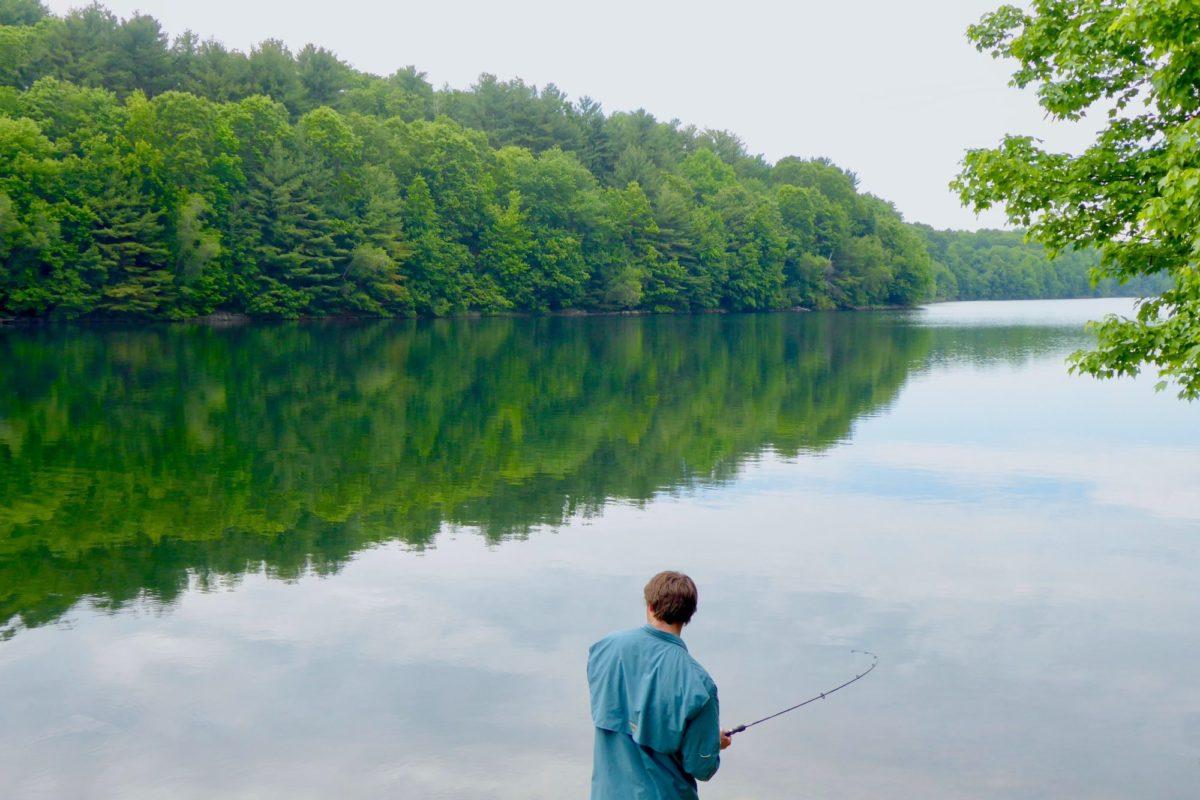 Ein Angler steht am Rande eines Sees im Wald und angelt.
