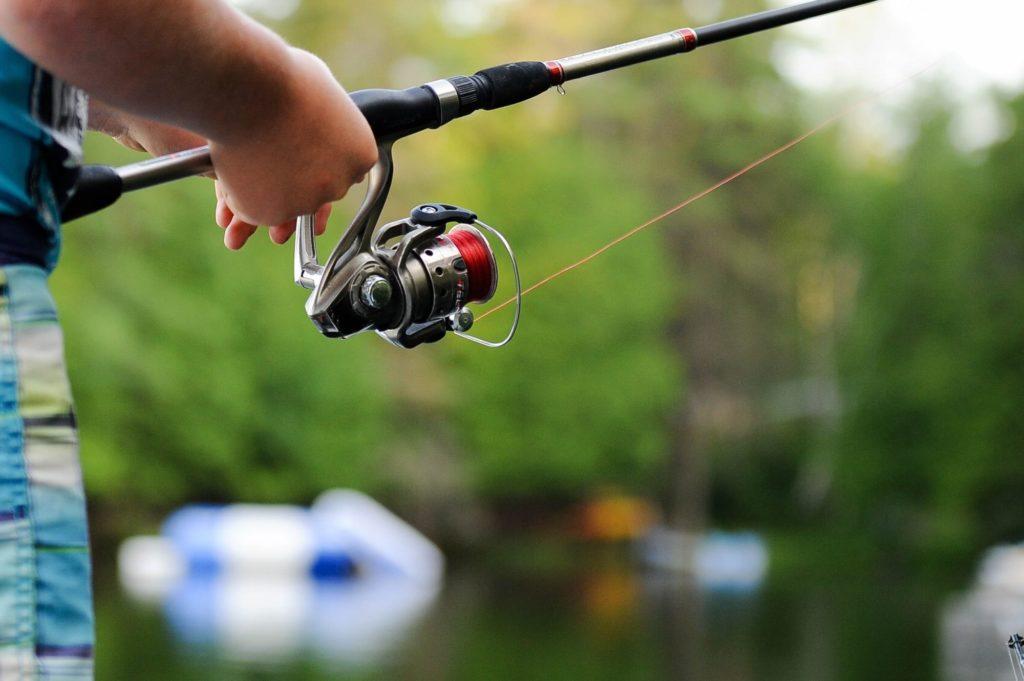 Corona-Pandemie sorgt für Boom im angeln. Mann steht mit Rute am Wasser.