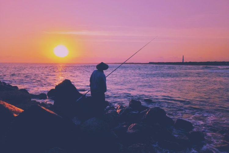 Ein angler steht mit Rute am Wasser und beobachtet den Sonnenuntergang