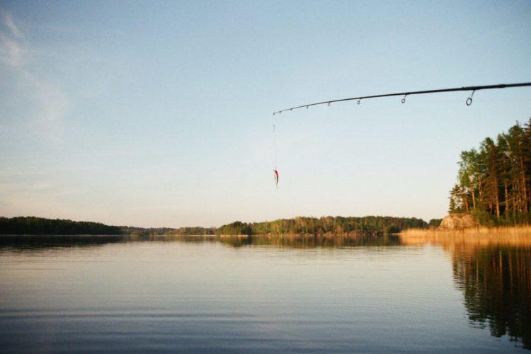 Ein angler steht am Wasser, zu sehen sind Wasser, Bäume, die Rute und ein kleiner Köder.