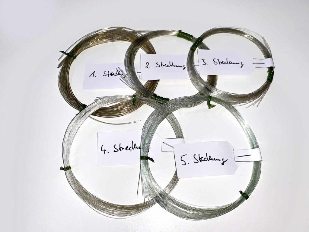 Nachdem das flüssige Granulat durch die Düsen gedrückt wurde, entsteht eine dicke Schnur (1. Streckung). Diese wird mehrfach gestreckt und somit dünner gezogen, um den gewünschten Durchmesser zu erhalten. Foto: F. von Nolting