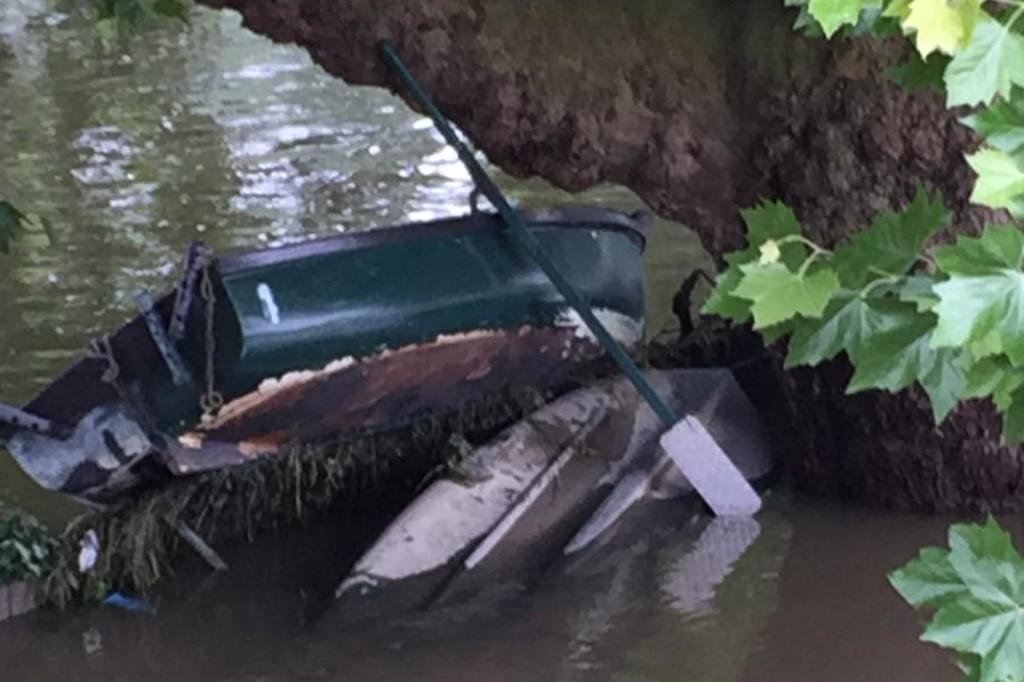 Ein kleines Angelboot von dem Hochwasser auf einen Baum aufgelaufen.