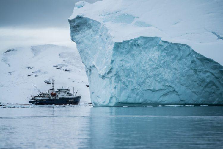 Auf dem Wasser fährt ein kleines Schiff hinter einen großen Eisberg.