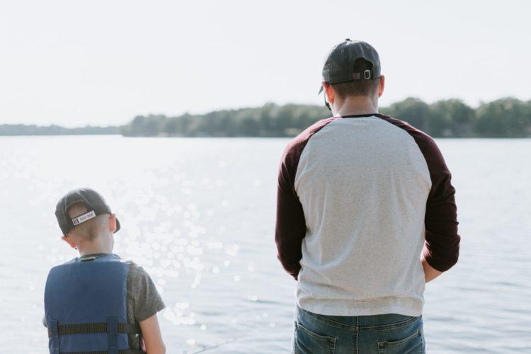 Vater und Sohn stehen nebeneinander und beobachten das Wasser.