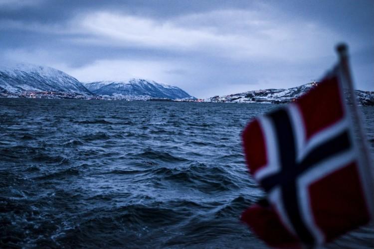 Im Vordergrund eine unscharfe norwegische Flagge aus dem Meer. Im Hintergrund Meer und am Horizont die verschneiten Berge und Lichter einer Stadt.