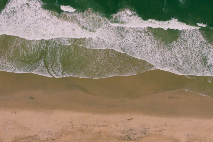 Vogelperspektive auf eine Strand und Meer.
